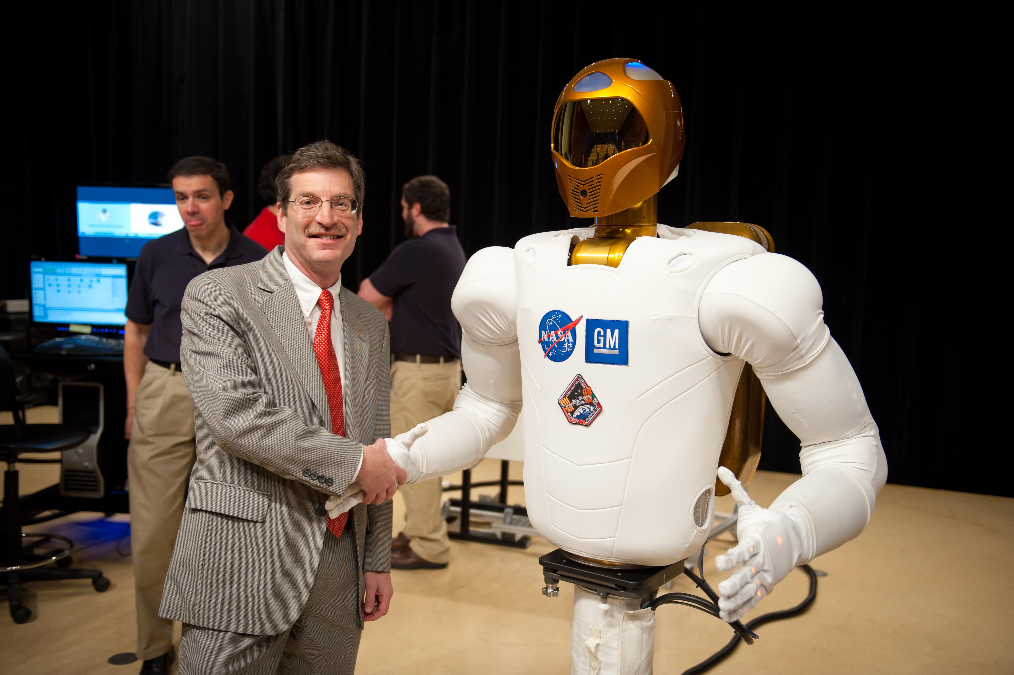 roboticsindustryassoc-president-jeff-burnstein-shakes-hands-with-gm-nasa-robonaut-2.jpg